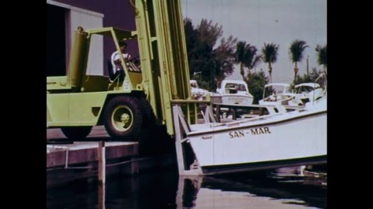 1970s: UNITED STATES: fork lift truck lowers boat into water by dock. Truck crashes into walls, tyres, and glass