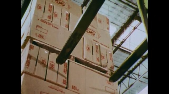 1970s: UNITED STATES: forklift truck moves to top of boxes. Truck lifts stack of boxes. Battery charge level.