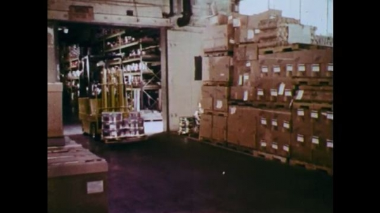 1970s: UNITED STATES: man drives truck inside warehouse. Lady drives forklift truck