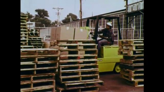 1970s: UNITED STATES: Man drives forklift truck. Truck moves boxes through narrow space. Man drops boxes on ground