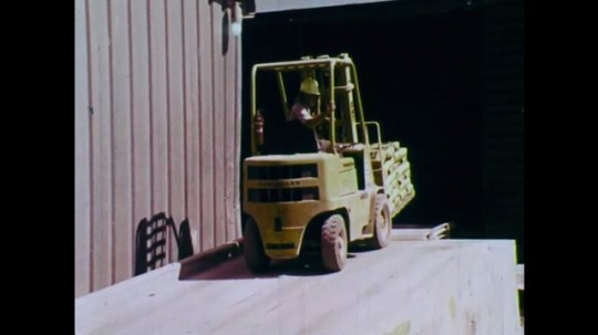 1970s: UNITED STATES: driver reverses truck. Boxes on truck. Truck unloads boxes.