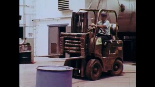 1970s: UNITED STATES: man drives truck. Man knocks container of liquid over. Boxes outside warehouse