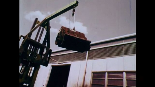 1970s: UNITED STATES: object swings from truck. Man drives truck. Lady with clipboard