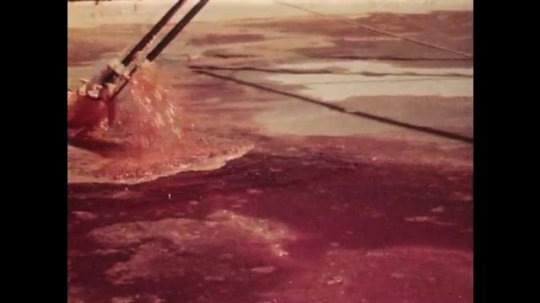 1950s: Large pool of red liquid (liquid sulfur).  Two rotating pipes spout more liquid sulfur into the pool.
