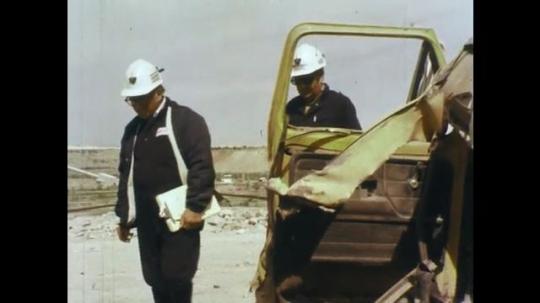 1970s: Men in hard hats inspect wreckage of truck.  Men walk past open truck door.  Men point.  Destroyed truck.
