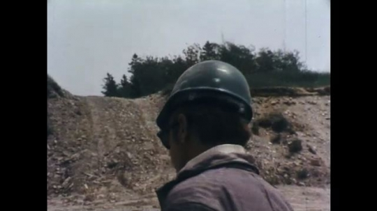 1970s: Man in hard hat turns.  Man looks down.  Men stand by explosives truck.  Man feeds wire into ground.  Man drops shell into hole in ground.