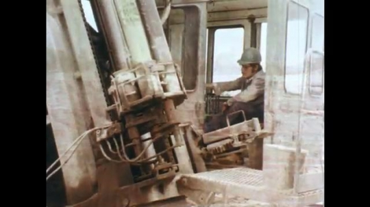 1970s: Man in hard hat inside heavy machinery.  Hand places shell in hole in the ground.  Man stands in metal shelter and presses buttons.  Men point and look at large rock pile.  Mining facility.