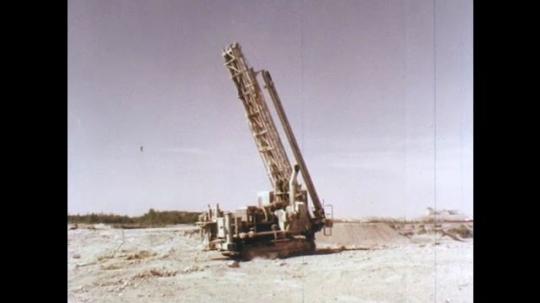 1970s: Machine moves along the edge of a pit.  Machine anchors itself.  Drill breaks through ground.  Machinery spins.  Man in hard hat pulls levers.