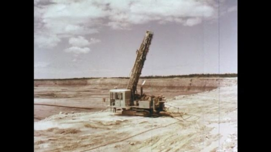 1970s: Machine sits at edge of a pit.  Man in hard hat feeds measuring tape into hole.  Hands feed tape off roll.  Tape moves through dirt.  Man looks down.  Man uses handle to withdraw tape.