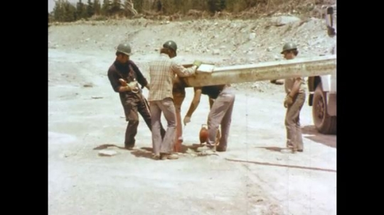 1970s: Men in hard hats stand with pipe coming from truck.  Men pull wires.  Man unwraps shell.  Explosives.  Knot in fuse wire.  Bag in hole.  Ropes tied.  White powder emptied in hole.