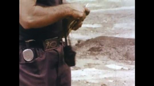 1970s: Man picks up shell.  Man weaves yellow string through and around shell.  Man lowers shell into hole in ground.  Men stand with pipe coming from truck.