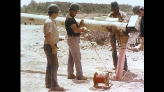 1970s: Men in hard hats stand near truck with pipe.  Men hold measuring tape and wire in hole.  Tube feeds into hole.  Man threads objects.  Man looks down.  Tube moves away.  Man picks up rock.