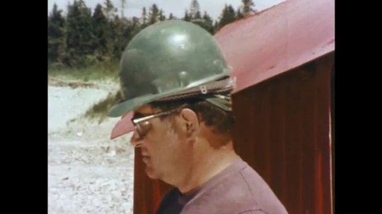 1970s: Men in hard hats turn.  Man wraps and drops shell into hole.  Measuring device with gauge.  Wires are held to device.  Man looks down.  Man points mirror at ground.  Thumbs press buttons.