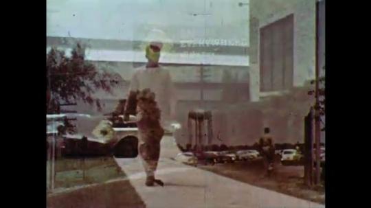 1960s: Man walks toward parking lot. Man walks towards building and encounters man walking out. The two men talk.