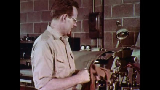 1960s: Man in machine shop wipes hands with cloth. Another man approaches and they talk.