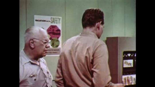 1960s: Two men talk in front of vending machine. One man puts arm around the other.