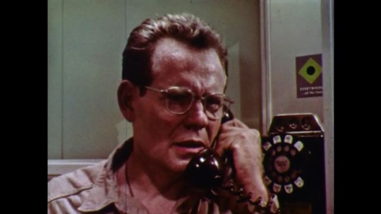 1960s: Man talks on phone in phonebooth. Hangs up phone and leaves the booth.