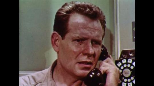 1960s: Man talks on phone.