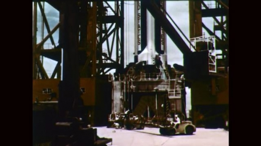 1960s: Uniformed men exit truck. Rocket ship on launch pad. Men work on rocket ship.