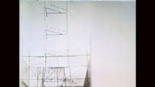 1960s: Scaffold and launch pad. Men observe rocket. Rocket launches. Men walk toward launch pad. Rocket climbs into sky.