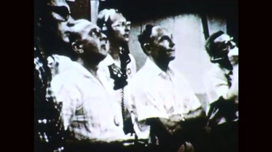 1960s: Men observe launch. Man with headset speaks. Men observe tools. Man places pipe in mouth.