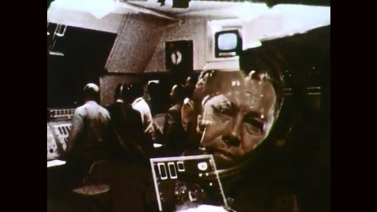 1960s: Men stand in control room. Rocket explodes. Men discuss blueprints.