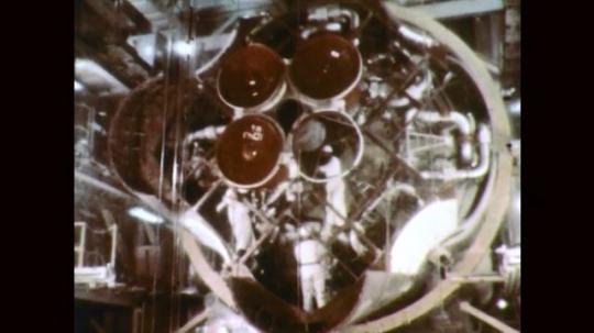 1960s: Uniformed men work on rocket engine.