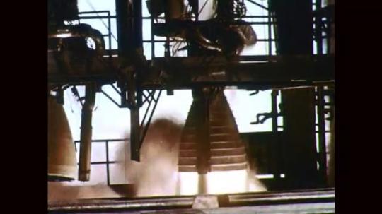 1960s: Rocket engine test fires. Men move rocket engine. Men adjust rocket engine.