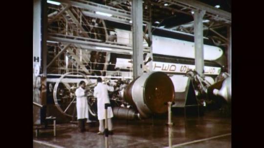 1960s: Men work on rocket engine. Men observe rocket booster. Man measures rocket boosters. Rocket Booster engine. Men adjust rocket booster.