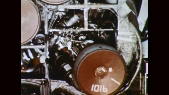 1960s: Man adjusts rocket booster. Man swivels rocket booster. Rocket engine booster. Man walks by rocket booster tank.