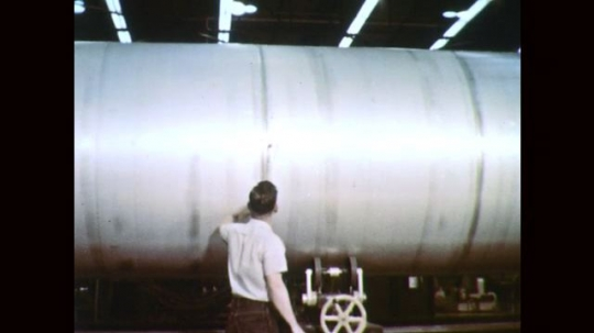 1960s: Man touches rocket booster tank. Man walks by rocket booster tank. Man inspects interior rocket booster tank.