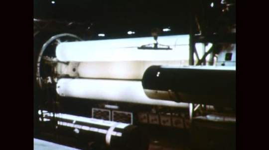 1960s: Rocket booster tank is moved by crane. Men work on rocket fuel tank. Rocket fuel tank.