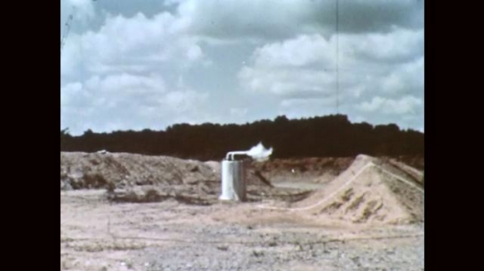 1960s: Fuel tank explodes. Man observes rocket booster tank.