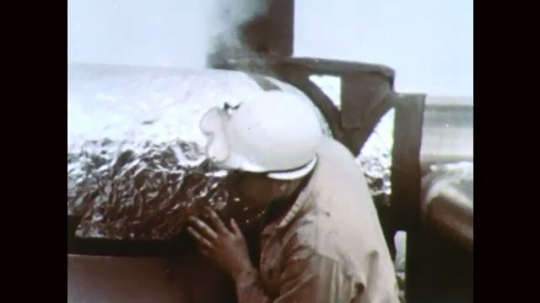1960s: Man inspects rocket booster. Rocket booster spews smoke. Rocket booster ignites on launch pad.