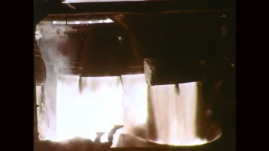 1960s: Rocket engines fire. Rocket booster engine fires from launch pad.