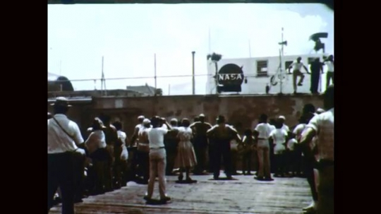 1960s: Crowd watches barge. Truck moves rocket from barge. Man watches rocket removal.