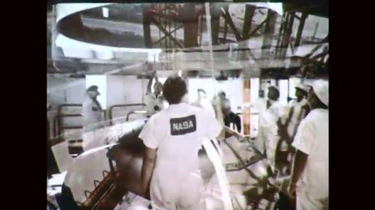 1960s: Men lower rocket nose cone. Men assemble rocket nose cone. Rocket in launch tower.