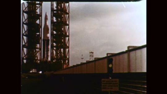 1960s: Rocket at launch site. Rocket in launch tower. Rocket booster tank in launch tower. Signal light flashes at launch site. Men work on rocket.