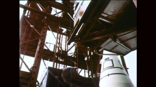 1960s: Gantry moves away from rocket. Rocket on launch pad. Launch tower and rocket. Storm clouds.