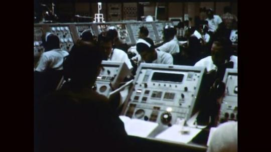 1960s: Men in control room. Men adjust paper in computers. Men at control panels.