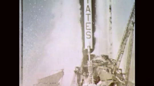 1960s: Rocket booster ignites. Rocket lifts off launch pad. Rocket flies toward sky.