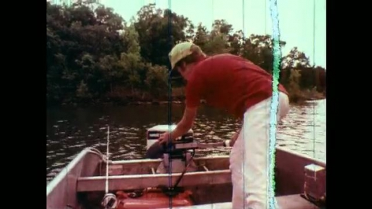1970s: Boy in boat pulls on starter rope of outboard motor. Boy sits down on boat bench. Outboard motor. Hand holds throttle and pulls starter rope of outboard motor.  Boy stands at back of boat.