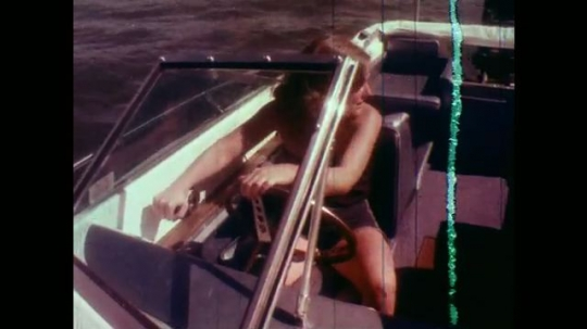 1970s: Woman steers boat. Motorboat moves slowly on choppy lake.