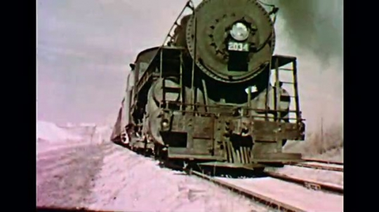 1950s: UNITED STATES: front view of slow moving steam train on tracks. Side view of train on tracks. Train lets off steam