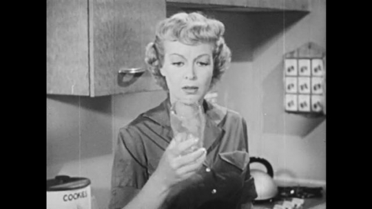 1950s: UNITED STATES: lady looks at glass in kitchen. Lady looks at floor. Lady looks at hands. Lady touches hair. Lady smiles
