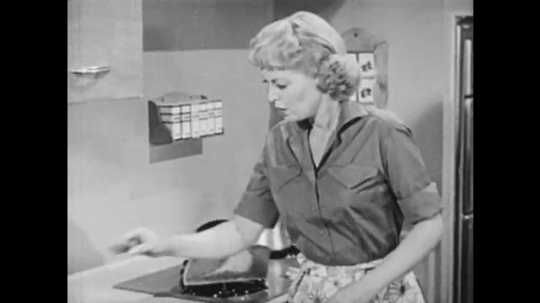 1950s: UNITED STATES: lady picks up pipe in kitchen. Lime scale inside pipe