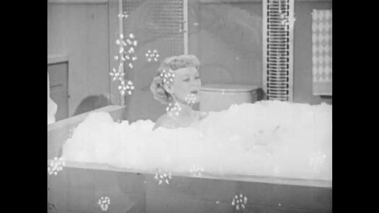 1950s: UNITED STATES: lady sits in bubble bath. Lady smiles.