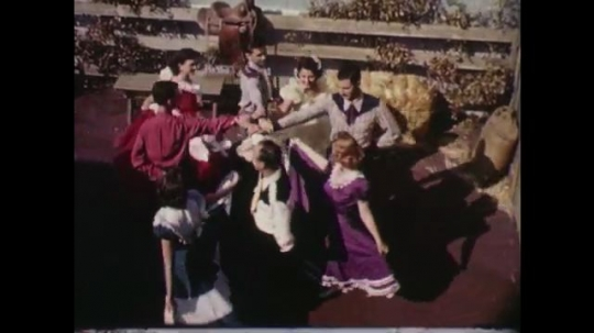 1960s: UNITED STATES: American western square dance in yard. People hold hands in circle. People dance together