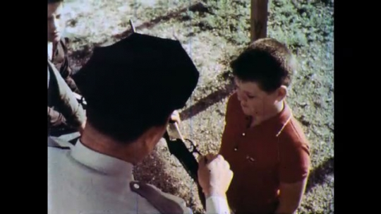 1960s: UNITED STATES: policeman shows gun to boy. Policeman educates children about gun safety. Boy listens