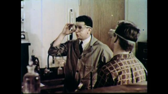 1960s: UNITED STATES: teacher wears goggles in class. Boys wear safety goggles in lesson